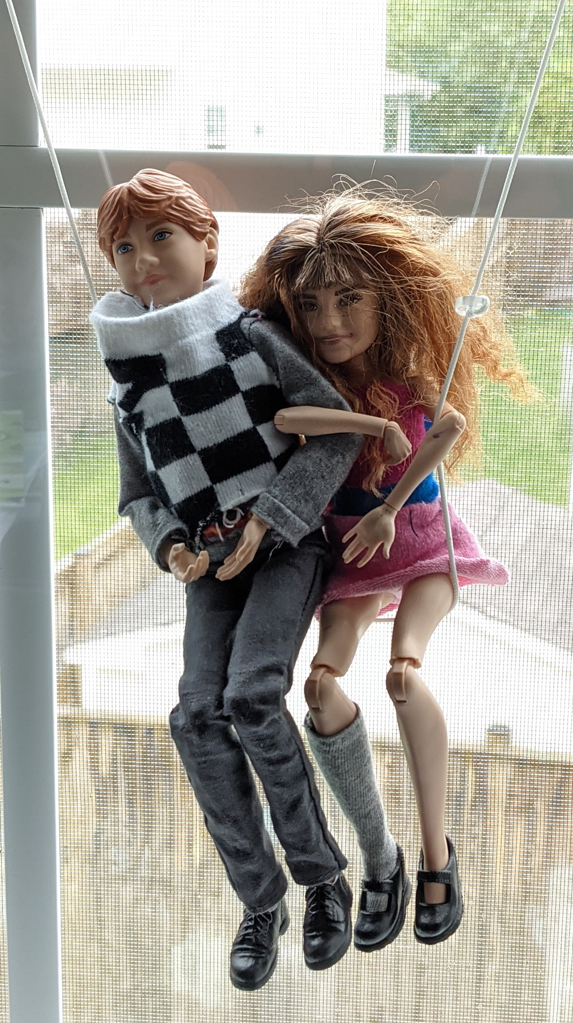 A photo of two dolls hanging on a string in front of a window as if on a swing